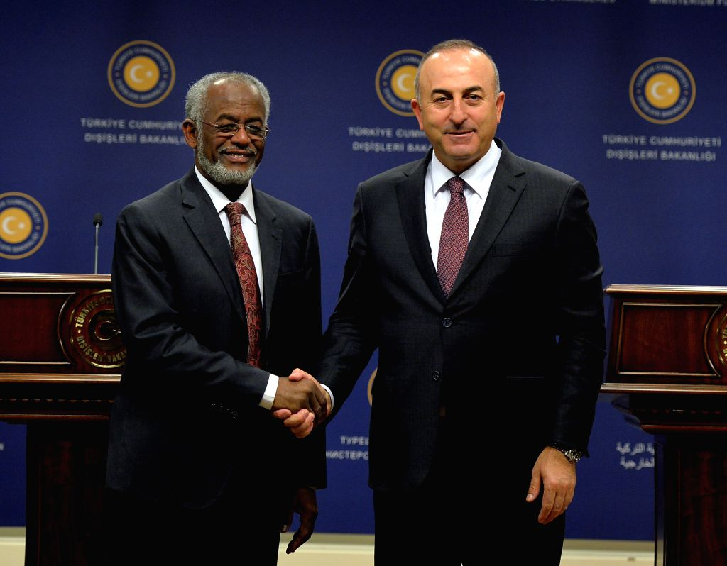 Turkish Foreign Minister Mevlut Cavusoglu (R) shakes hands with his Sudanese counterpart Ali Karti during a joint press conference in Ankara, Turkey, on April 10, ... - Mevlut Cavusoglu