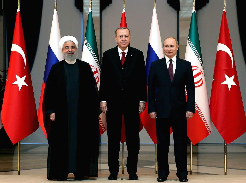 ANKARA, April 4, 2018 - Turkish President Recep Tayyip Erdogan (C), Russian President Vladimir Putin (R) and Iranian President Hassan Rouhani pose before their meeting at the Presidential Palace in ... - Hassan Rouhani