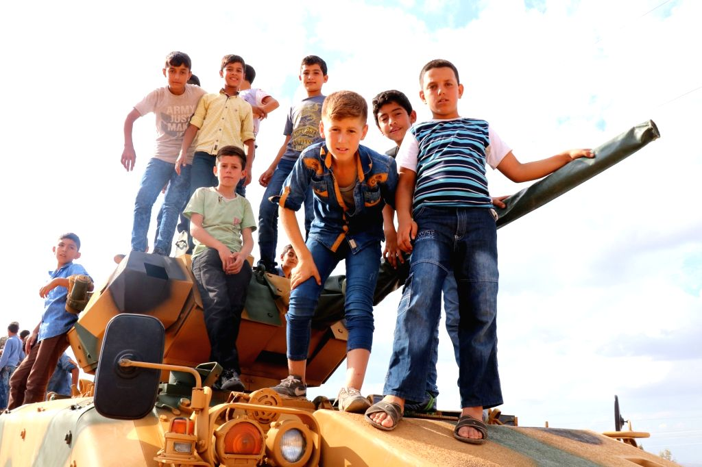 ANKARA (TURKEY), Oct. 11, 2017 Boys stand on top of a Turkish army vehicle as a military convoy passes by their village on the Turkish-Syrian border line in Reyhanli, Hatay province, ...