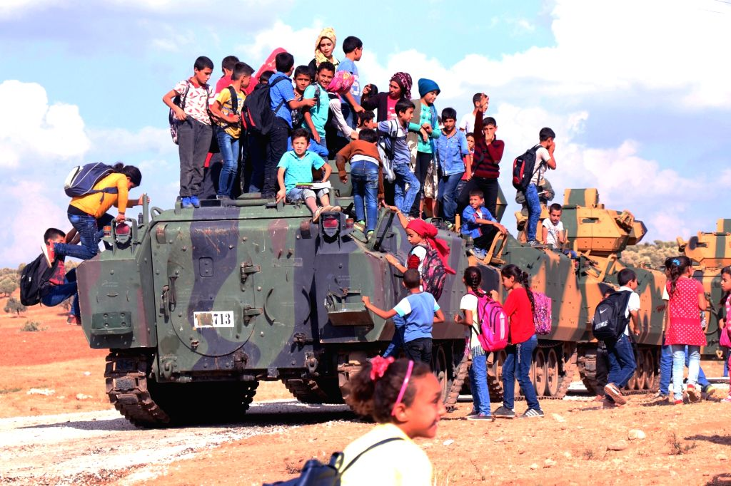 ANKARA (TURKEY), Oct. 11, 2017 Local children stand on top of a Turkish army vehicle as a military convoy passes by their village on the Turkish-Syrian border line in Reyhanli, Hatay ...