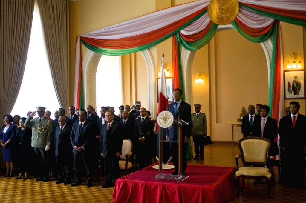Madagascar's President Hery Rajaonarimampianina (C), Prime Minister Kolo Roger and the newly appointed ministers salute to the national song in the Presidency - Kolo Roger