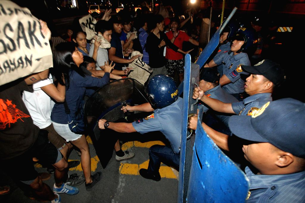 Anti-riot policemen clash with activists during a protest rally against the Enhanced Defense Cooperation Agreement (EDCA) in front of the U.S. Embassy in Manila, the ...