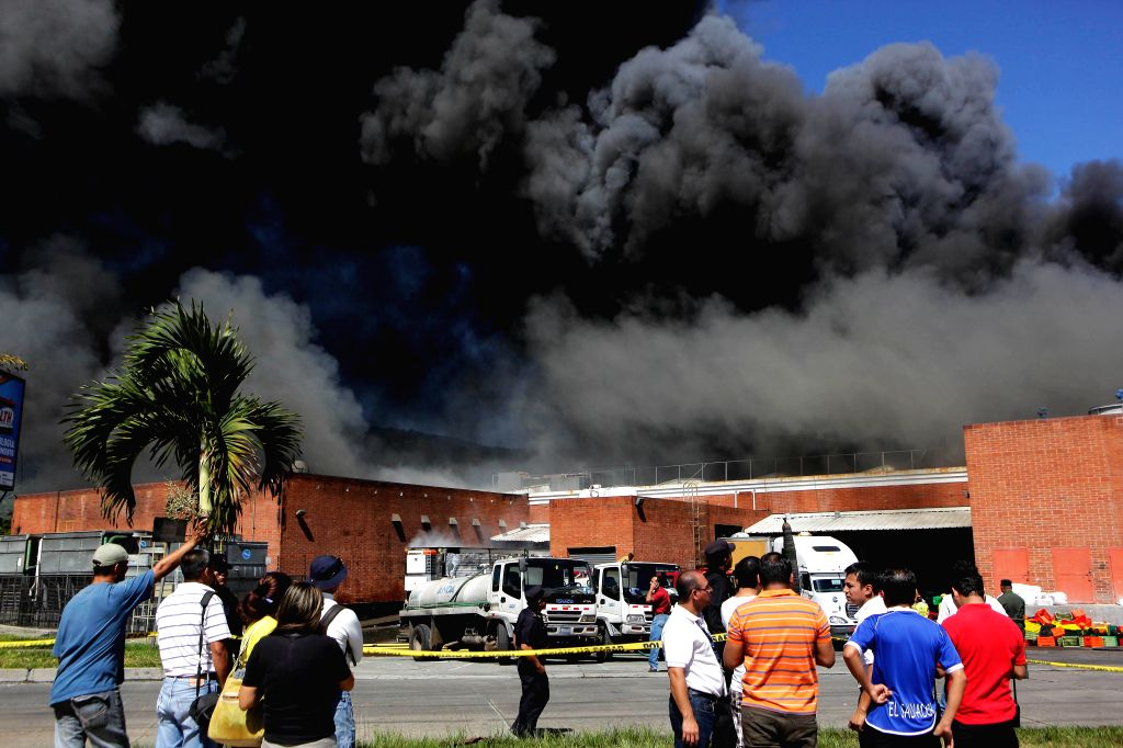 People gather outside the Las Cascadas Commercial Center where a fire broke out in the town of Antiguo Cuscatlan, 12 km away from San Salvador, capital of .
