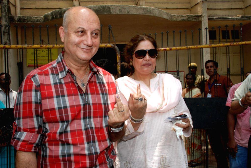 Anupam Kher with his wife Kiran Kher after casting their votes in Mumbai. - Anupam Kher and Kiran Kher