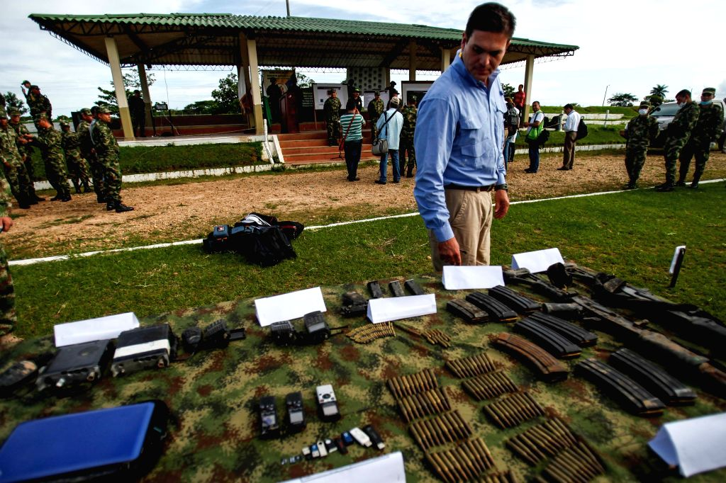 Colombian Defense Minister Juan Carlos Pinzon looks at seized guns and objects of members of the National Liberation Army (ELN) after an operation of the military ... - Juan Carlos Pinzon