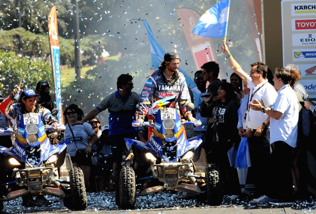 Argentina's driver of the quad category Marcos Patronelli (C, Front) of Yamaha team, celebrates his third title with his brother Alejandro Patronelli (L) at the end ...
