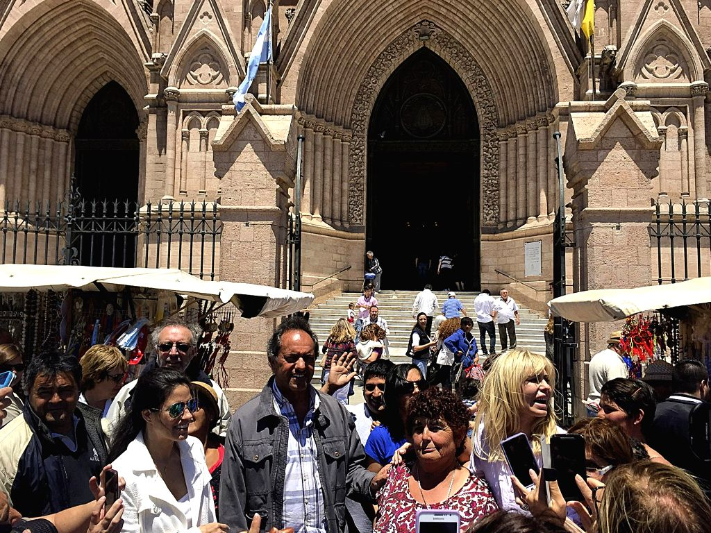 Argentina's ruling Front for Victory party presidential candidate Daniel Scioli (3rd L) poses with people during his visit to the Basilica of Our Lady of Lujan in ...