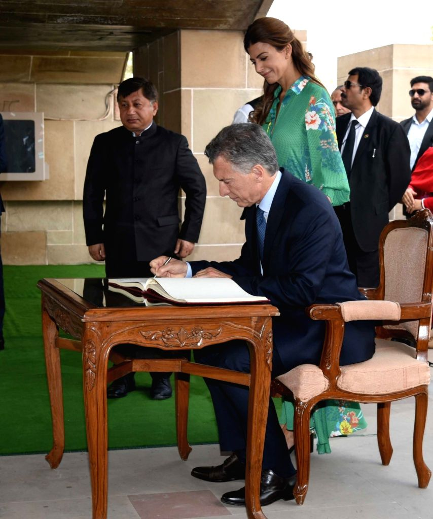 Argentine President Mauricio Macri signs the visitors' book at Rajghat, on Feb 18, 2019. Also seen Argentine first lady Juliana Awada.