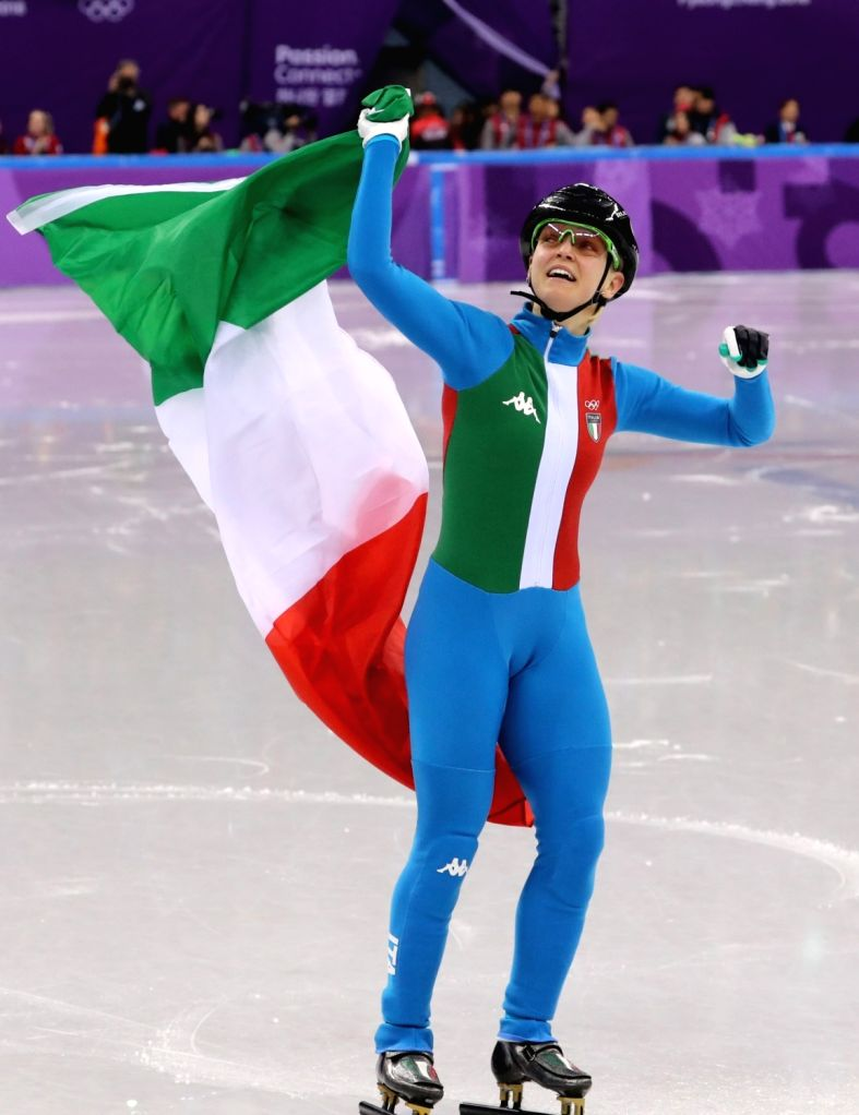 Arianna Fontana of Italy waves the Italian flag after winning the gold in the women's 500 meter short track speed skating race at the Gangneung Ice Arena in Gangneung, on the east coast, ...