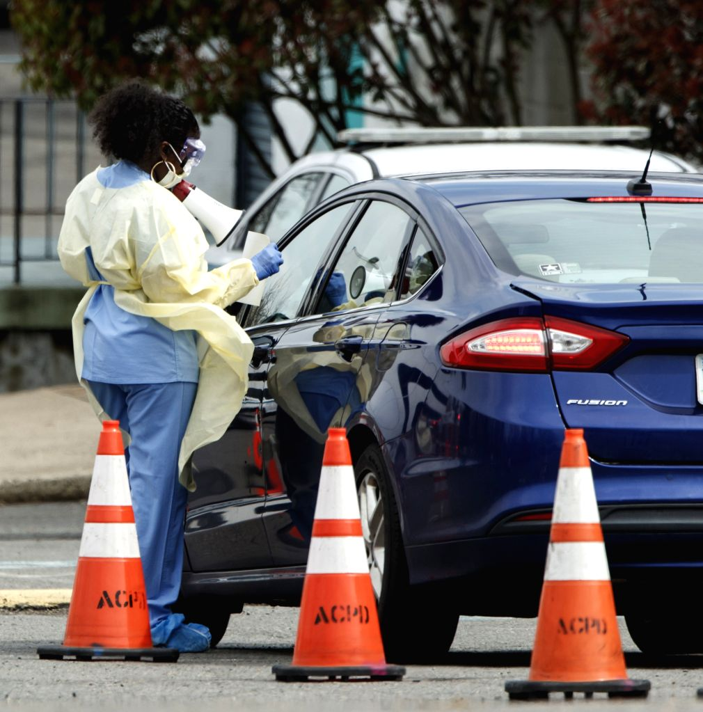 ARLINGTON (U.S.), March 19, 2020 A health worker directs a driver at a drive-through COVID-19 testing location set up by the Virginia Hospital Center in Arlington, Virginia, the United ...
