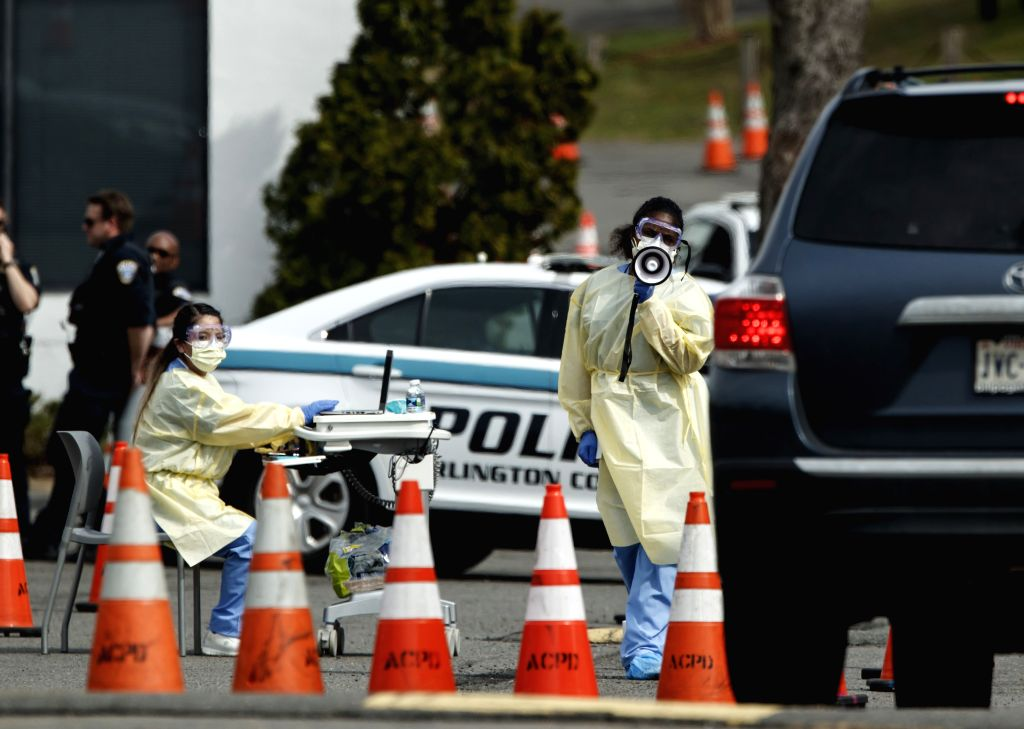 ARLINGTON (U.S.), March 19, 2020 Health workers are seen at a drive-through COVID-19 testing location set up by the Virginia Hospital Center in Arlington, Virginia, the United States, on ...