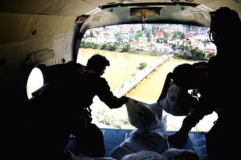 Armed forces personnel drop therapeutic food packets in the flood affected areas of Srinagar on Sept 11, 2014.