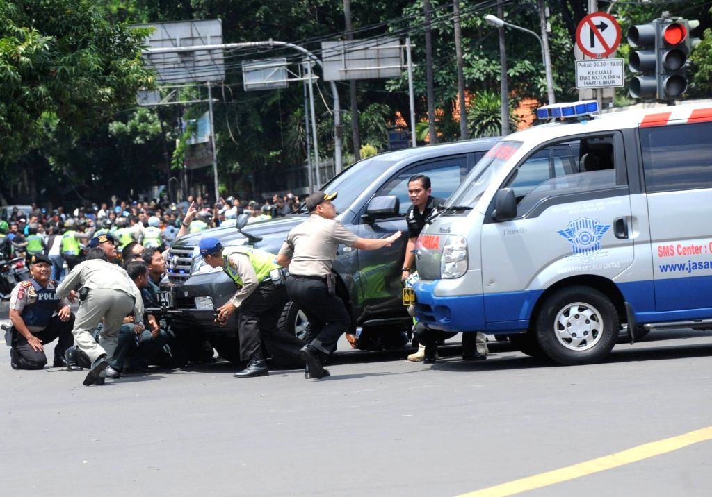 Armed police officers hide behind cars during the fire exchanges on a street in Jakarta, Indonesia, Jan. 14, 2016. One policeman and three civilians were killed, ...