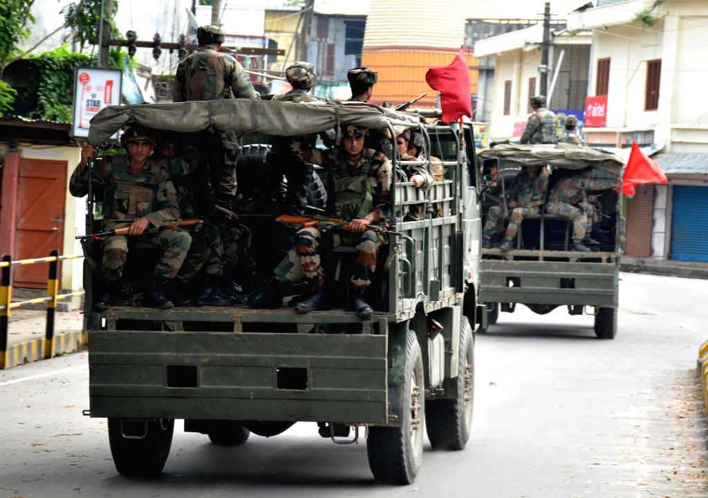 Army conducts a flag march in Assam's troubled Golaghat district of Assam near the border with Nagaland on Aug 21, 2014. Curfew was imposed in the district Wednesday after three people died when ...