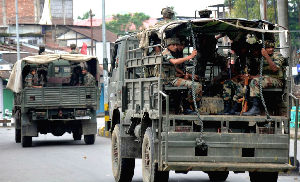 Army conducts a flag march in Assam's troubled Golaghat district of Assam near the border with Nagaland on Aug 21, 2014. Curfew was imposed in the district Wednesday after three people died when police fired at protestors, who took to the streets in