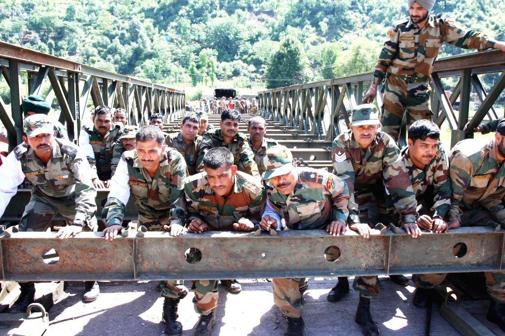 Army personnel build a bridge over Poonch river on a war footing as the earlier bridge, on the Jammu-Poonch National Highway connecting Poonch with rest of the country was washed away in a flash ...