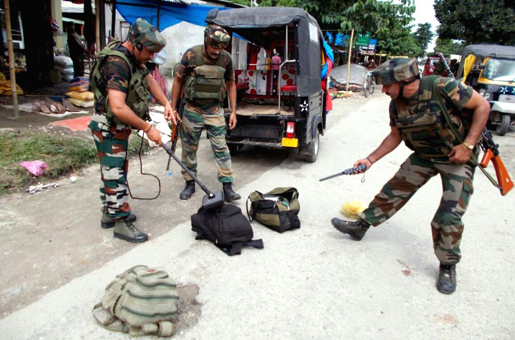 Army personnel check bags left by a group of militants in Kokrajhar terror attack on Aug 5, 2016. At least 12 civilians were killed on Friday when militants in military fatigues opened ...
