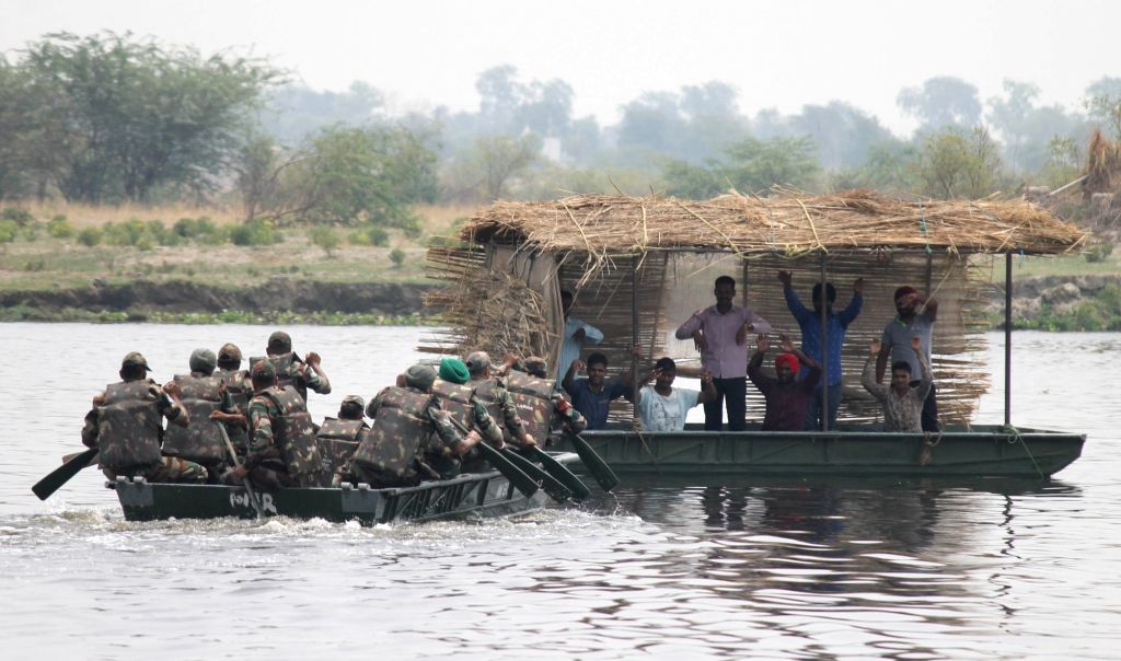 Army soldiers participate in a mock drill organised to brace-up for flood relief on the banks of Yamuna river in Mathura on June 27, 2016.