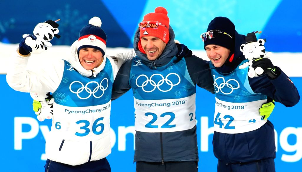Arnd Peiffer (C) of Germany, Michal Krcmar (L) of the Czech Republic and Dominik Winisch of Italy celebrate after crossing the finish line to win gold, silver and bronzer medals, ...