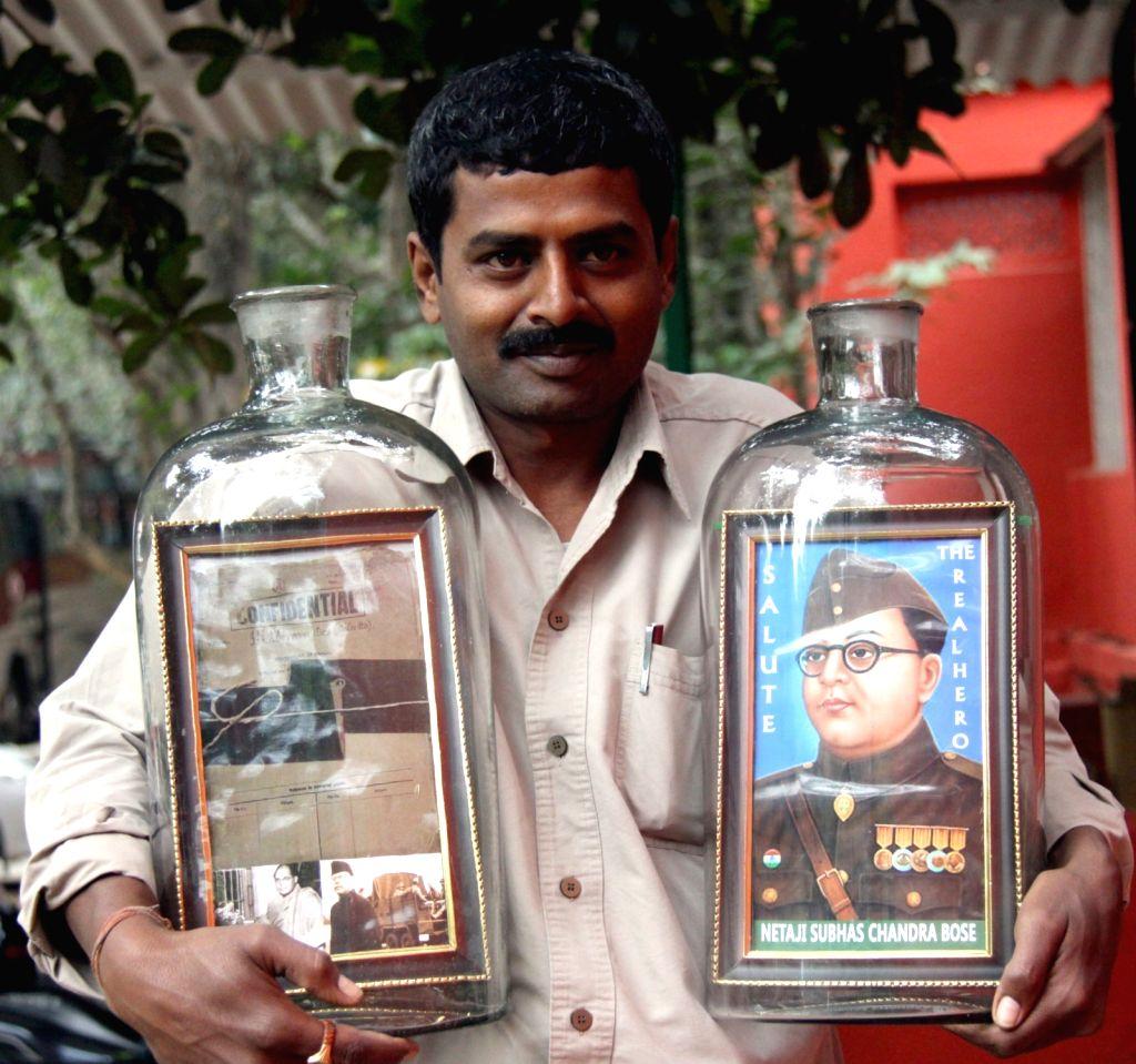 Artist Basavaraj S Gowda display his creativity by placing a photo frame of Netaji Subhash Chandra Bose inside a bottle on the eve of his birth anniversary, in Bengaluru on Jan 22, 2016. - Basavaraj S Gowda