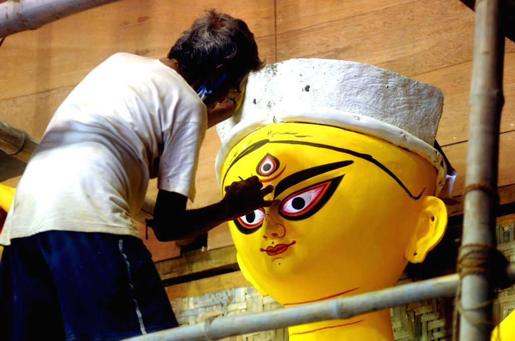 Artist gives finishing touches to an idol of Goddess Durga at the Baghbazar Sarbojanin ahead of Durga Puja festival in Kolkata on October 18, 2020.