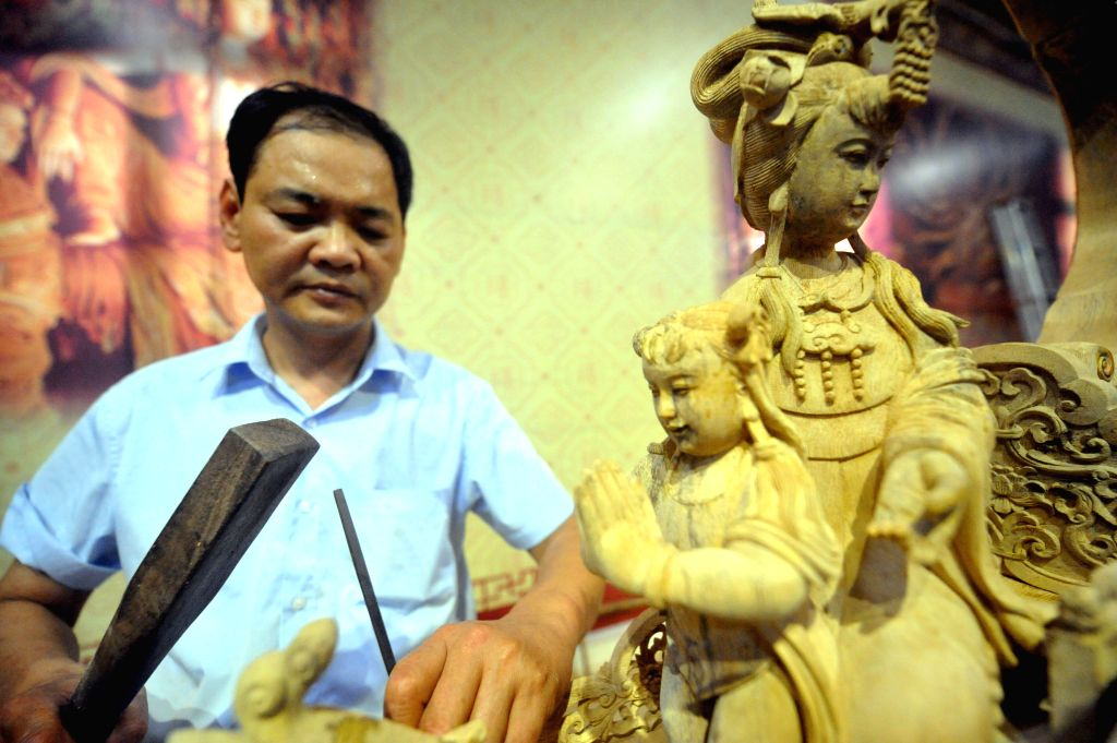 Artist Li Dinghua works on a wood sculpture during a wood art show in Xianyou, southeast China's Fujian Province, June 25, 2015. A wood art show was held in Duwei ... - L