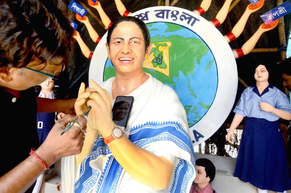 Artist Mintu Paul gives fishing to the clay of West Bengal Chief Minister Mamata Banerjee at community Puja pandal ahead of Durga Puja festival in Kolkata on October 01, 2021. - Mintu Paul and Mamata Banerjee