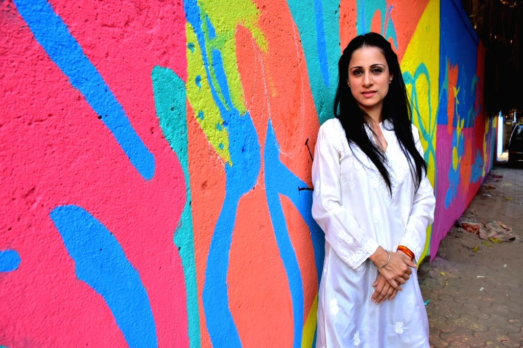 Artist Rouble Nagi stands in front of the wall painted by her in Mumbai on Feb 17, 2018. As part of the initiative - 'Misaal Mumbai', Rouble Nagi has painted over 285 slum houses in the city. ... - Rouble Nagi
