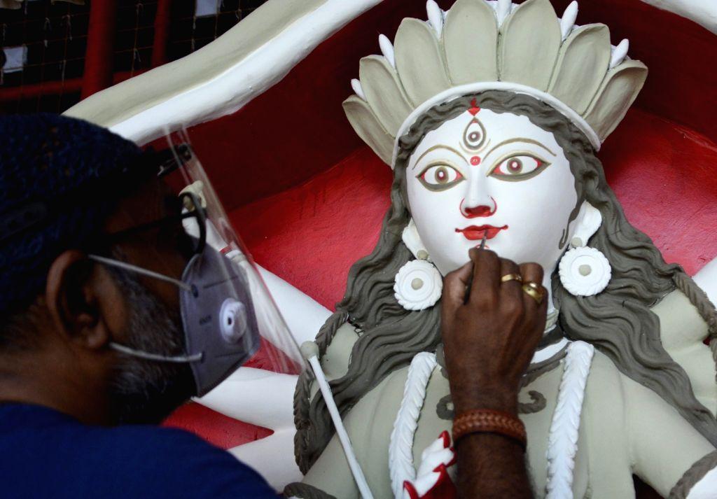 Artist Susanta Paul gives finishing touches to an idol of Goddess Durga at a comunnity Puja pandal on the eve of Durga Puja celebrations, in Kolkata on Oct 14, 2020. - Susanta Paul