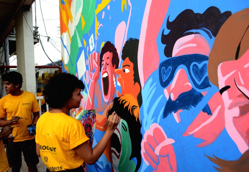 Artistes paint the inside wall of Eden Gardens ahead of the first Day-Night test match between India and Bangladesh, in Kolkata on Nov. 17, 2019.
