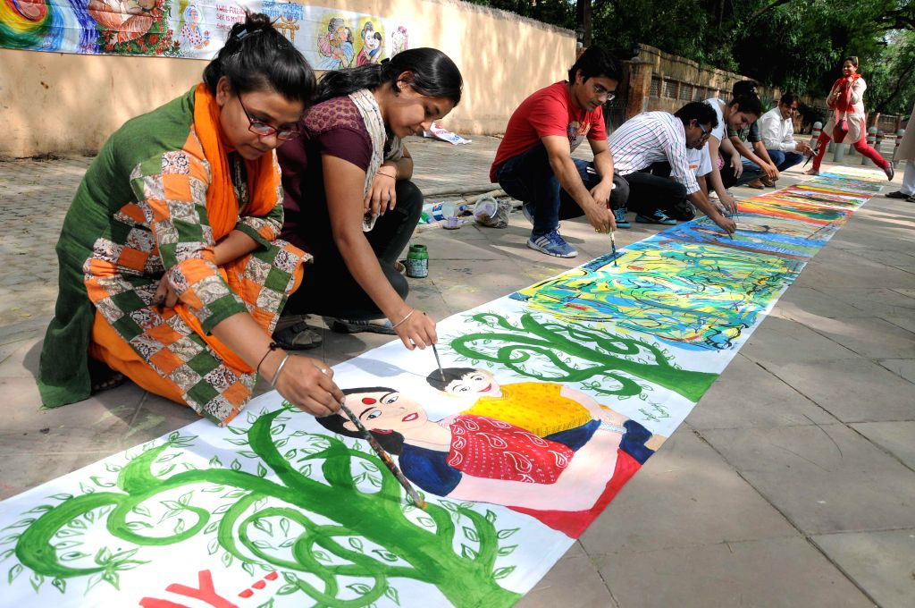 Artists and members of Health Education and Environment Awareness Society paint on Mother's Day at Jantar Mantar in New Delhi on May 11, 2014.