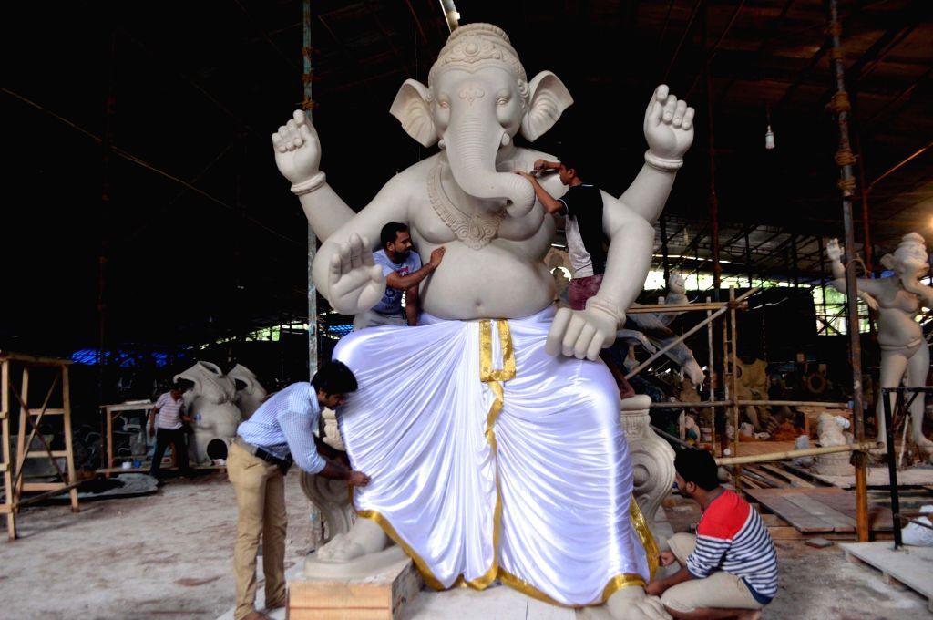 Artists busy making an idol of lord Ganesha ahead of Ganesh Chaturthi, at a Mumbai workshop on July 1, 2018.
