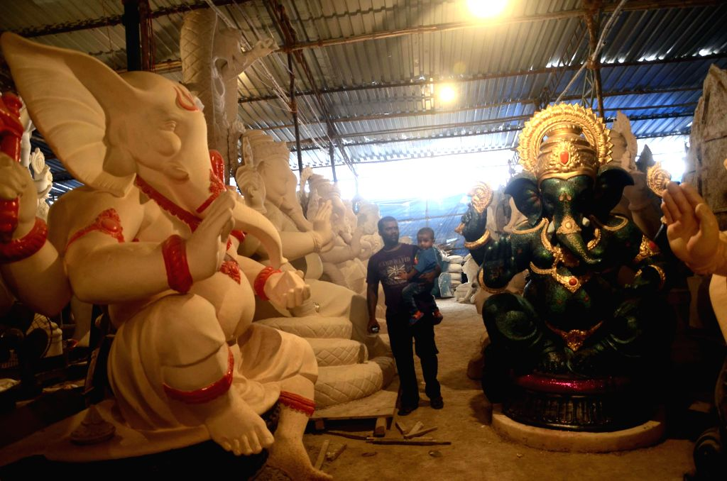 Artists busy making idols of lord Ganesh at a Mumbai workshop ahead of Ganesh Chaturthi on July 19, 2014.