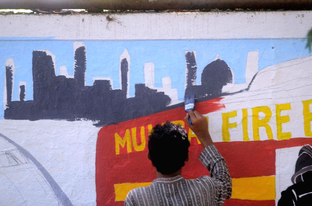 Artists busy painting a wall in Mumbai on May 15, 2017.