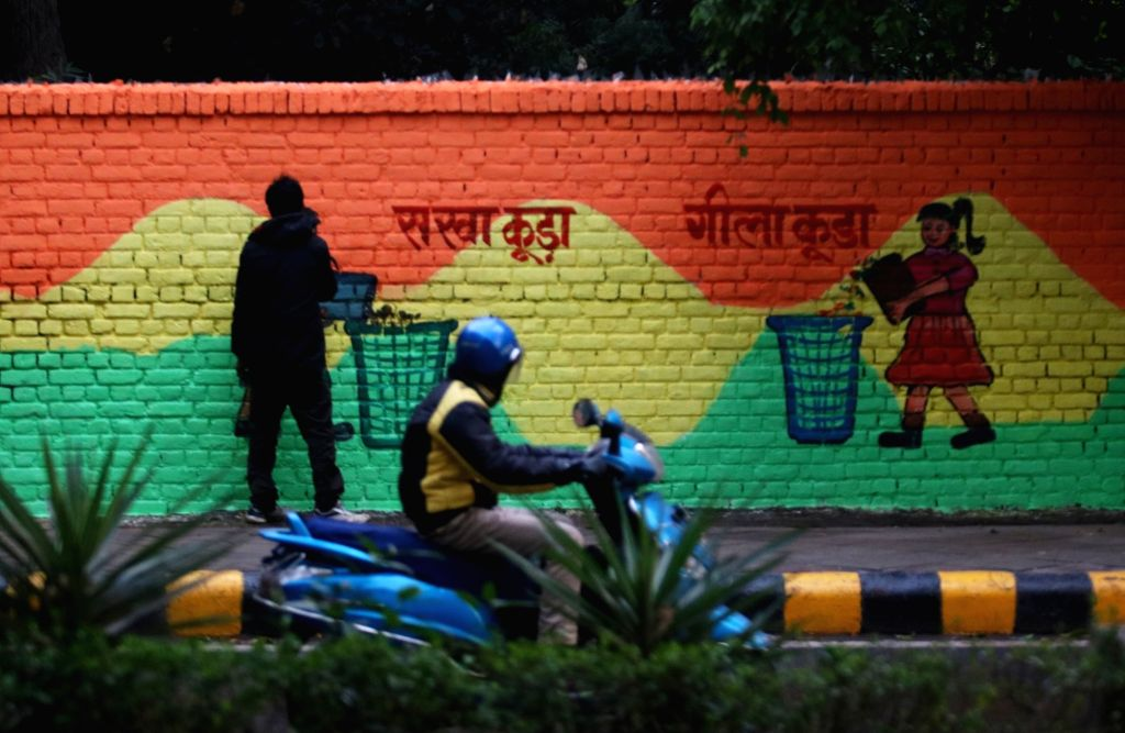 Artists busy painting a wall urging people to use different dustbins for different kinds of waste, in line with the Central Government's Swachha Bharat Mission in New Delhi, on Jan 21, ...