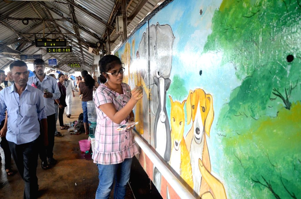 Artists busy painting on the foot over bridge at Mumbai's Bandra railway station on June 11, 2017.