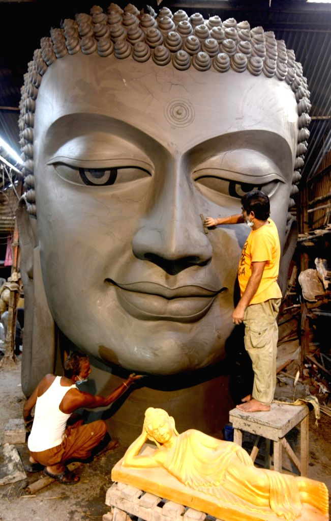 Artists busy working on the head of a 100 ft tall Buddha statue at Kumartuli workshop which is to be shipped to Goa, in Kolkata on Aug 13, 2020.