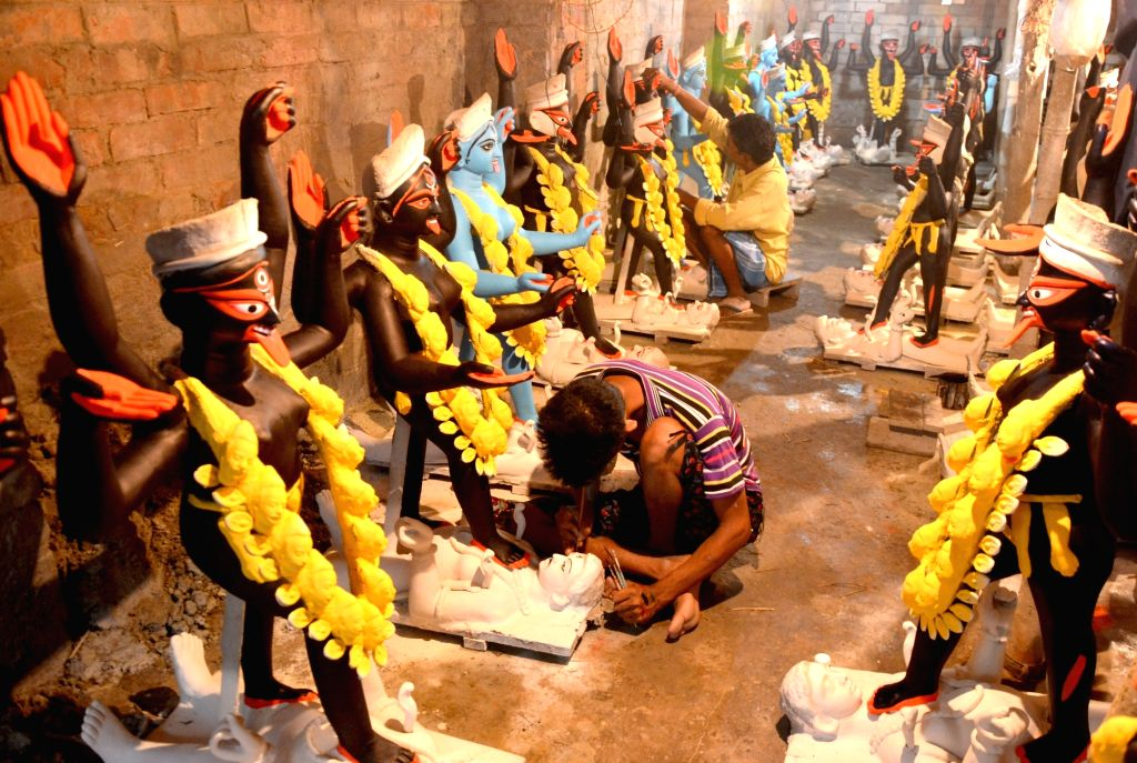 Artists give finishing touch to idols of Goddess Kali ahead of Kali Puja in Kolkata on Oct 10, 2017.