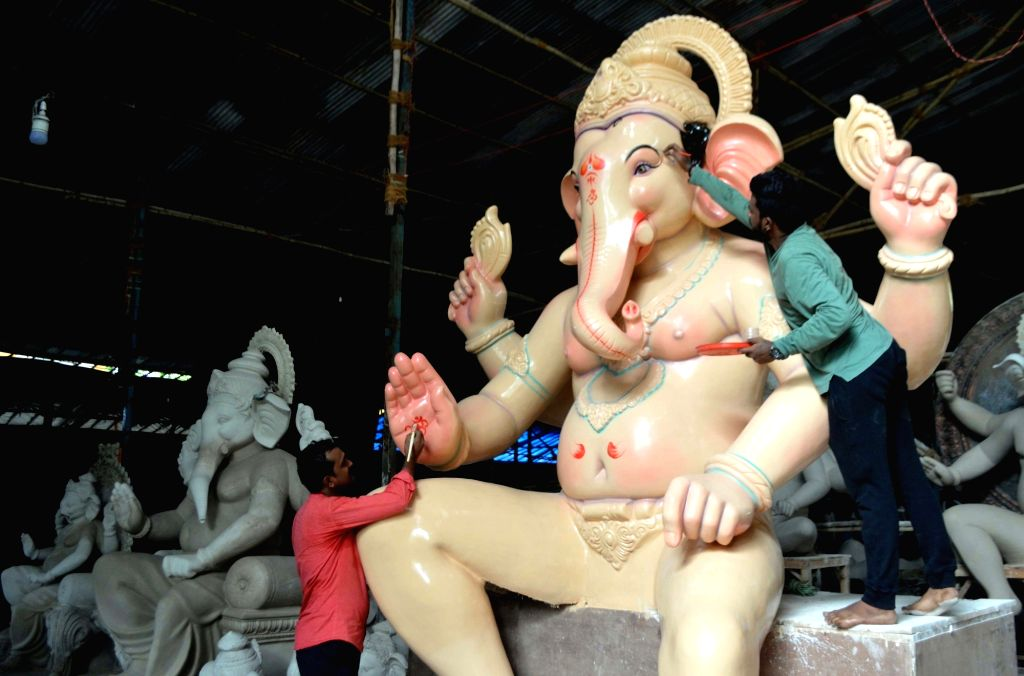 Artists give finishing touches to an idol of lord Ganesha ahead of Ganesh Chaturthi, at a Mumbai workshop on July 1, 2018.