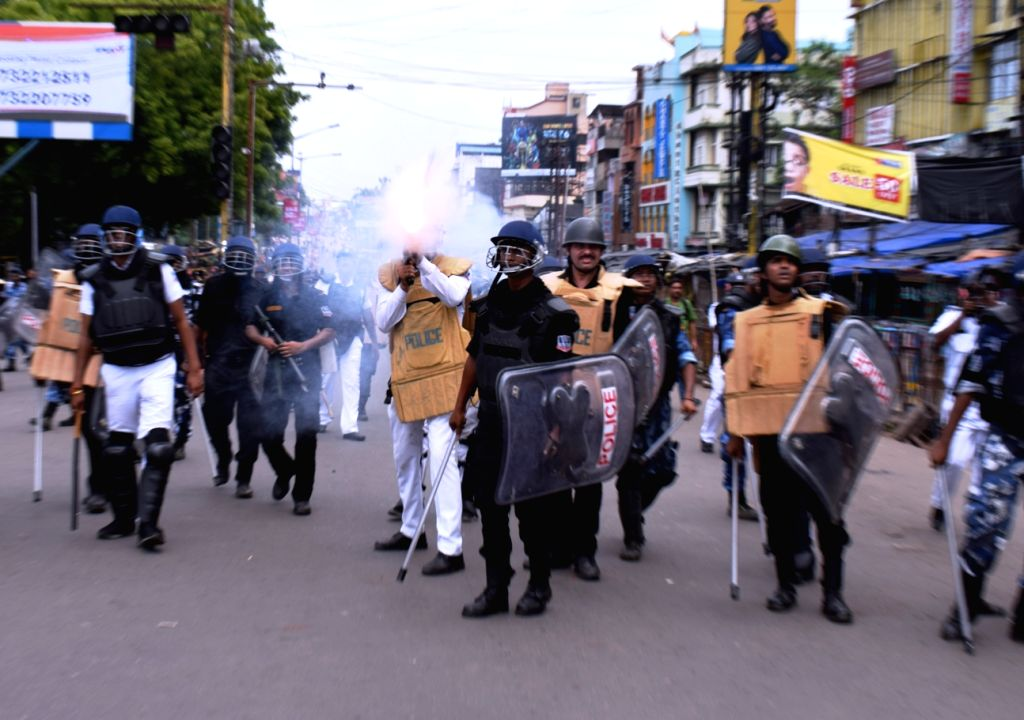 Asansol: Police fires tear gas shells to disperse an irate mob after a BJP-called a rally to submit deputation on the cut-money issue before the Asansol Municipal Corporation in West Bengal turned violent, in Asansol on July 5, 2019. (Photo: IANS)