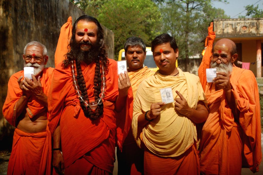 Ascetic show their voter's identity card after casting their votes at a polling booth during the ninth phase of 2014 Lok Sabha Polls in Varanasi on May 12, 2014.