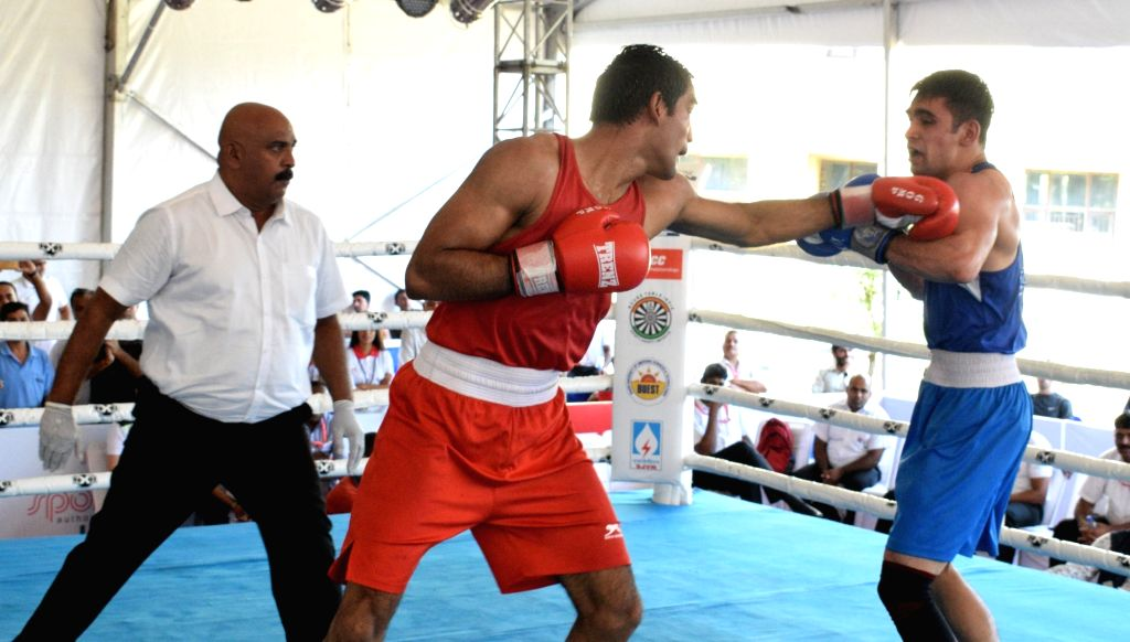 Ashish Chaudhary of Himachal Pradesh in action against Rohit Tokas of Railways during a quarter-final match in the 75 kg category of the 4th Elite National Men's Boxing Championship at Baddi ... - Ashish Chaudhary