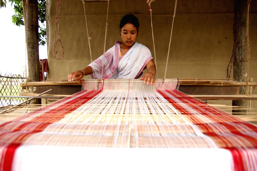 A woman weaves  traditional Assamese gamacha - towel - ahead of Rongali Bihu celebrations in Nagaon of Assam on March 27, 2015.
