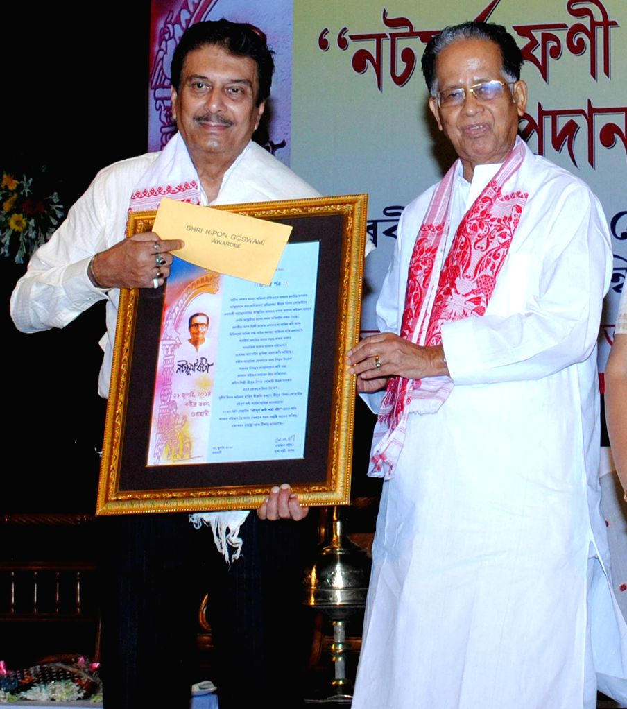 Assam Chief Minister Tarun Gogoi felicitates eminent actor Nipon Goswami with Natasurjya Phani Sharma Award 2014 at Rabindra Bhawan in Guwahati on July 31, 2014. - Tarun Gogoi and Nipon Goswami