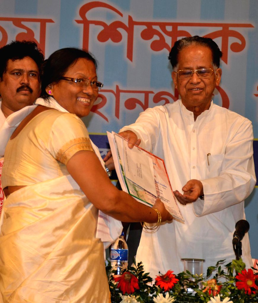 Assam Chief Minister Tarun Gogoi felicitates a teacher during a programme organised on Teachers' Day in Guwahati on Sept 5, 2014. - Tarun Gogoi