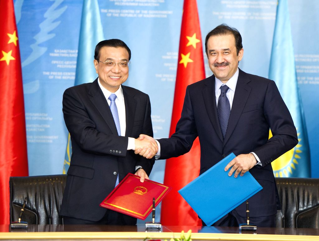 Chinese Premier Li Keqiang (L)and his Kazakh counterpart Karim Masimov attend a signing ceremony of bilateral cooperation documents in Astana, Kazakhstan, Dec. 14, ..