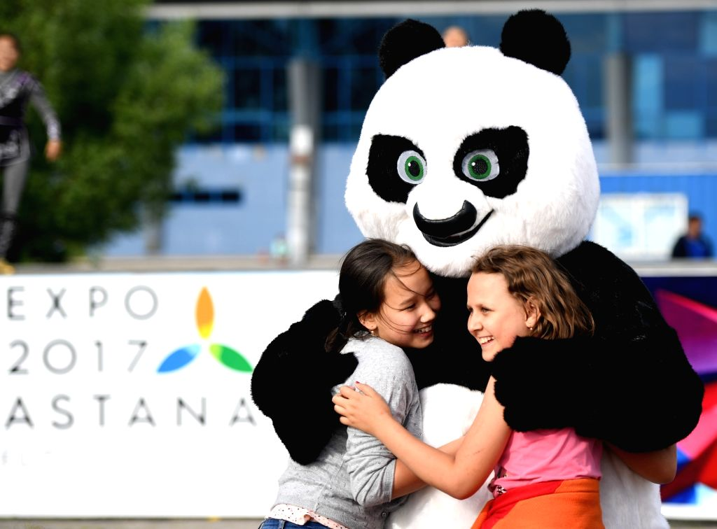 ASTANA, June 6, 2017 - Girls play with a dancer wearing panda costume during a performance of Sam Ruk dance group from Eurasian University in Astana, Kazakhstan, June 5, 2017.