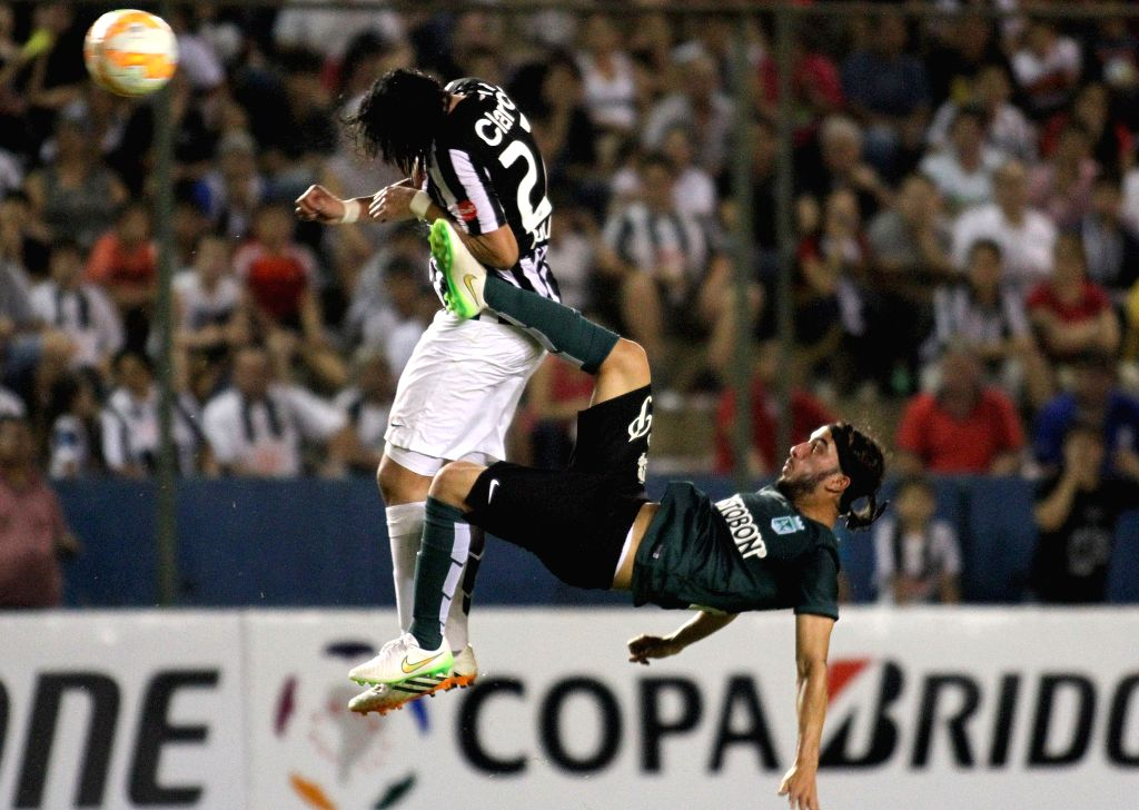 Libertad's Osmar Molinas (L) of Paraguay vies for the ball with Atletico Nacional's Sebastian Perez of Colombia during the match of Libertadores Cup, at Nicolas ...