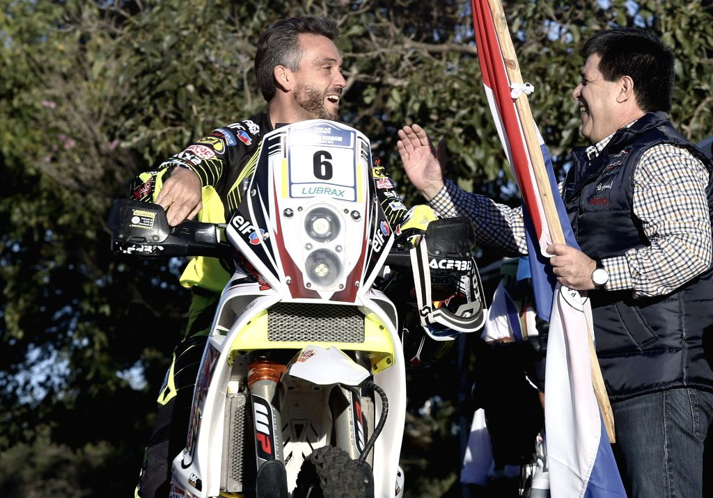 Paraguay's President Horacio Cartes (R) greets David Casteu (L) of France during the symbolic start of the Dakar Rally in Asuncion, capital of Paraguay, on July ...