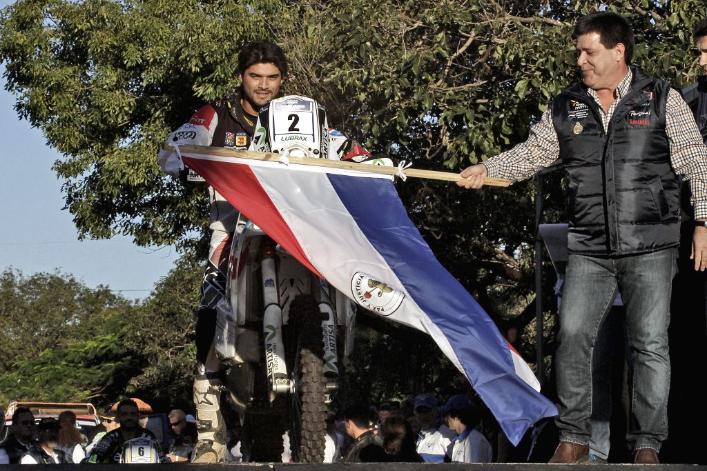 Paraguay's President Horacio Cartes (R) participates in the symbolic start of the Dakar Rally in Asuncion, capital of Paraguay, on July 20, 2014. The Dakar Series .
